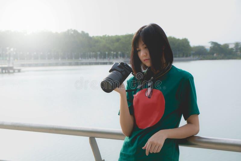 Le den unga kvinnan som använder en kamera för att ta fotoet utomhus arkivfoto
