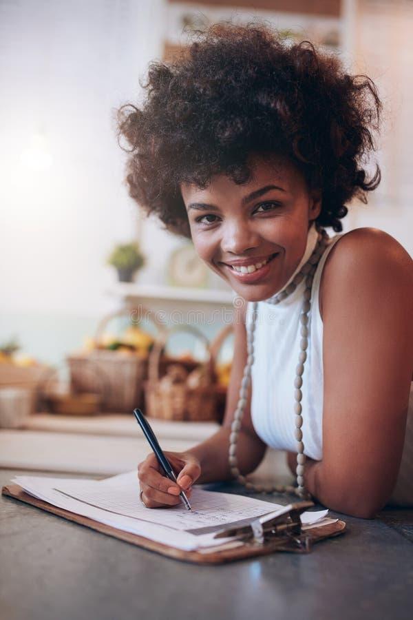 Le den unga kvinnan som arbetar i en fruktsaftstång arkivbilder