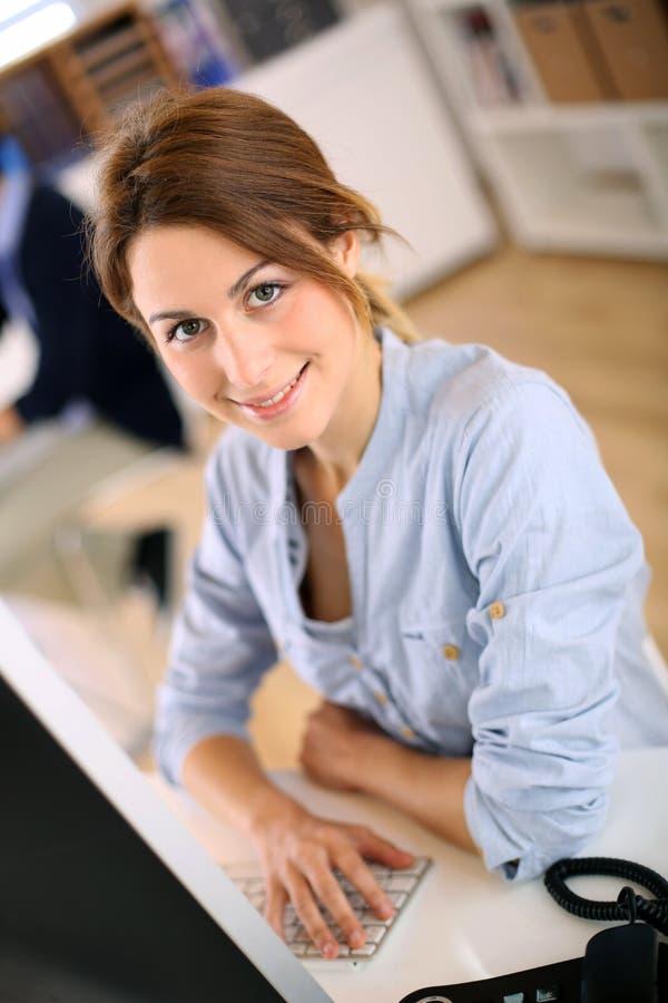 Le den unga kvinnan som arbetar med händer på tangentbordet arkivfoto