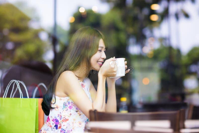 Le den unga kvinnan som dricker kaffe i kafé, shoppa arkivbild