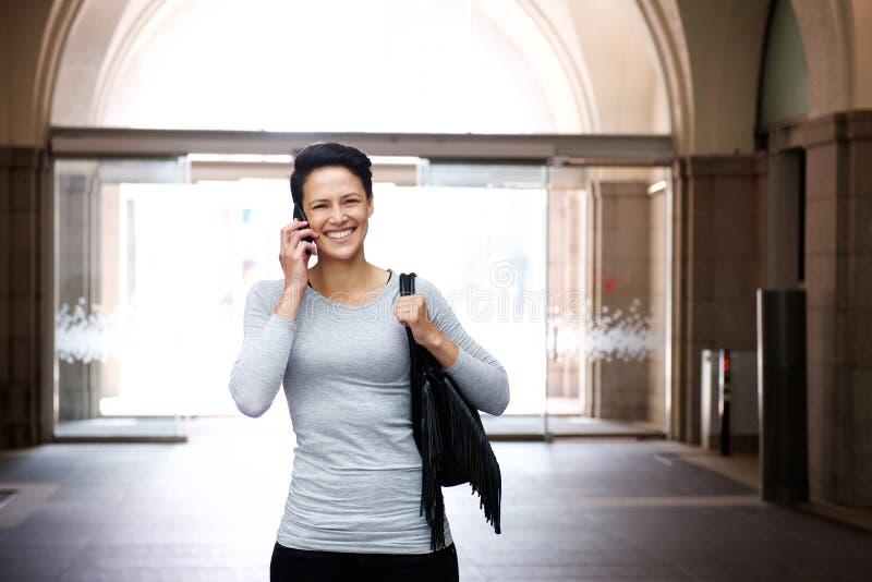 Le den unga kvinnan som går med mobiltelefonen och påsen arkivbild