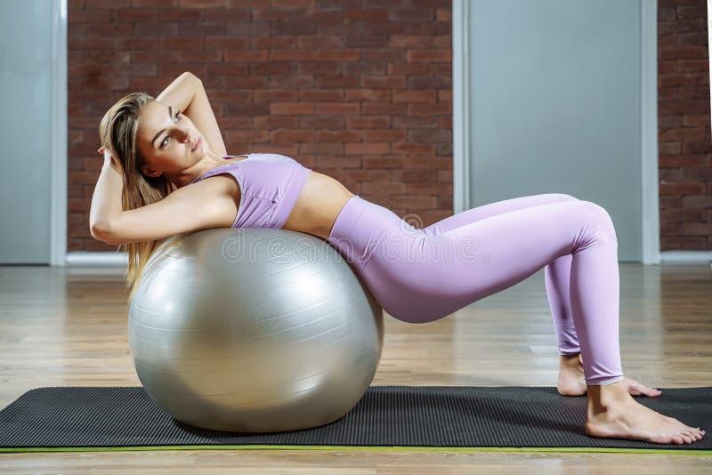 Le den unga kvinnan som gör buk- knastrande på konditionboll i en pilatesgrupp arkivbilder