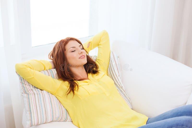 Le den unga kvinnan som hemma ligger på soffan arkivfoto
