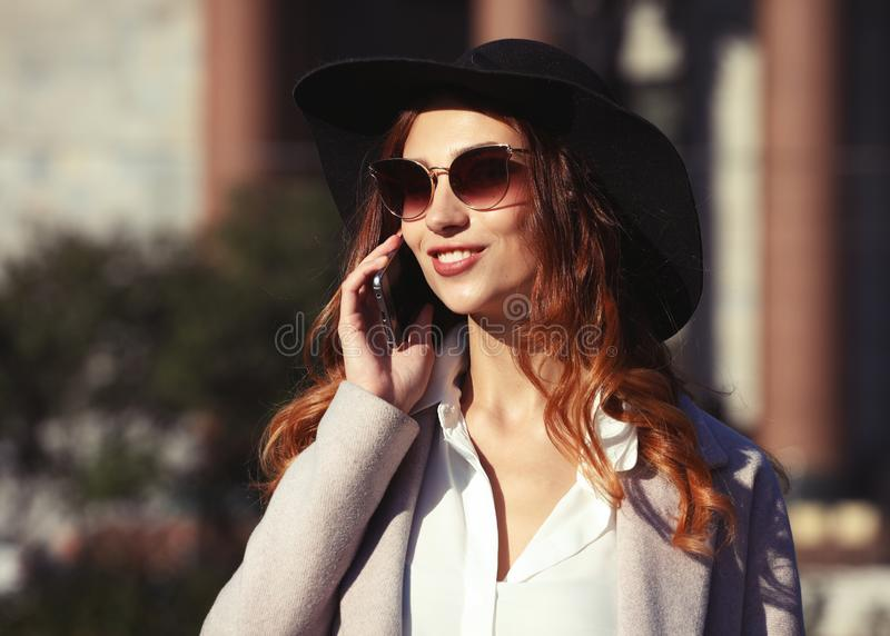 Le den unga kvinnan som kallar och talar på smartphonen i auten fotografering för bildbyråer