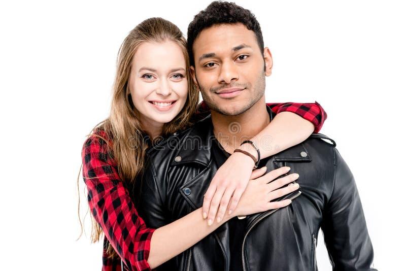 Le den unga kvinnan som kramar den stiliga mannen i läderomslag royaltyfri foto