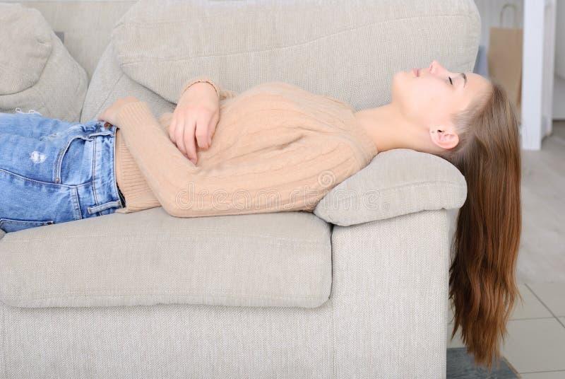 Le den unga kvinnan som ligger på soffan royaltyfri fotografi