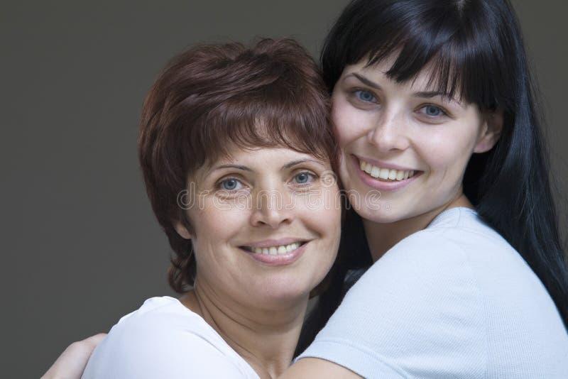 Le den unga kvinnan som omfamnar hennes moder arkivfoton