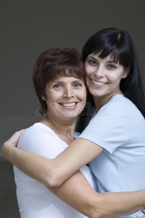 Le den unga kvinnan som omfamnar hennes moder fotografering för bildbyråer