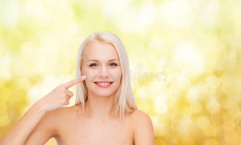 Le den unga kvinnan som pekar på hennes kind arkivbild