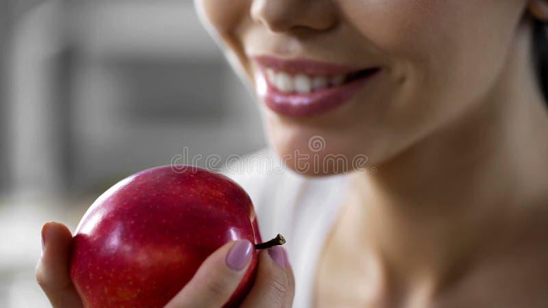 Le den unga kvinnan som rymmer det nya röda äpplet efter genomkörare, låg-kalori frukt royaltyfri fotografi