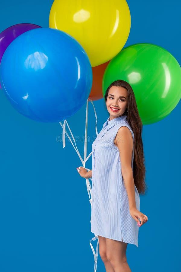 Le den unga kvinnan som ser färgrika luftballonger för kamera som och för innehav isoleras över blått fotografering för bildbyråer