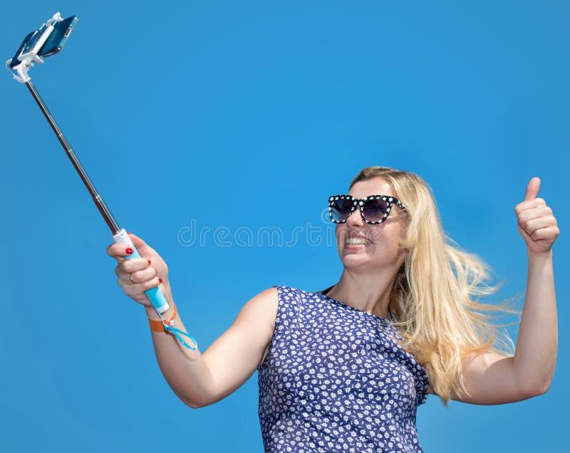 Le den unga kvinnan som tar selfie med smartphonen på stranden royaltyfri bild