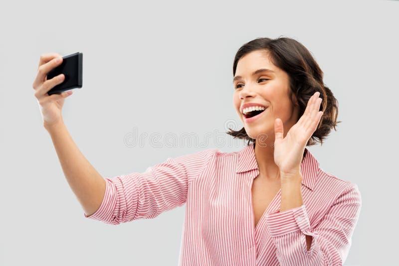 Le den unga kvinnan som tar selfie vid smartphonen royaltyfri foto