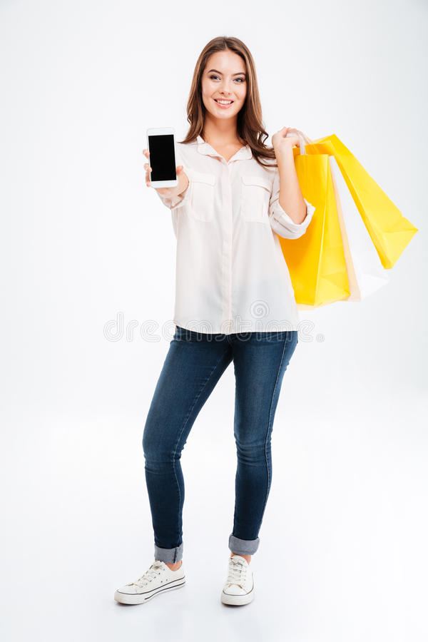 Le den unga kvinnan som visar smrtphone- och innehavpåsar för tom skärm arkivbild
