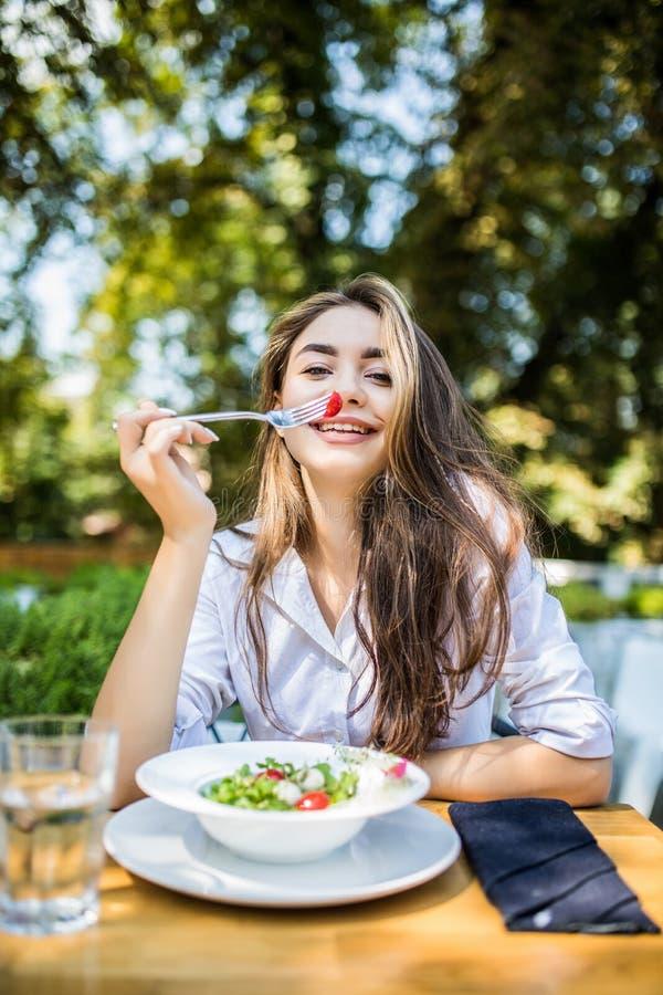 Le den unga kvinnan tycker om sallad för den nya grönsaken på kafét, har lunch efter arbete, uppehällen som bantar, äter endast s fotografering för bildbyråer