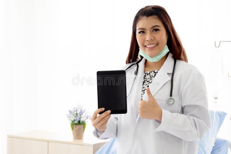 Le den unga kvinnliga tandläkaren eller läkaren bär det vita laget med stetoskopanseende och att rymma minnestavlan och tummar fö royaltyfria foton