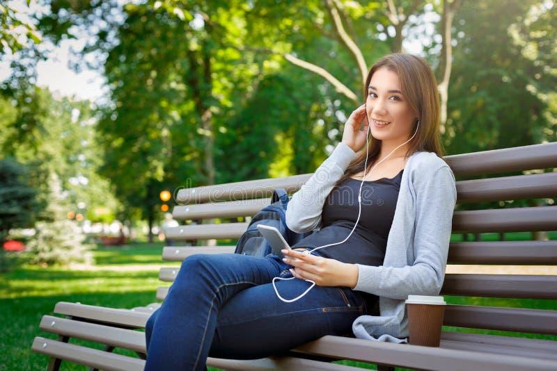 Le den unga kvinnligIT-studenten i hörlurar Lyssna till musik och dricka kaffe i parkera royaltyfria foton
