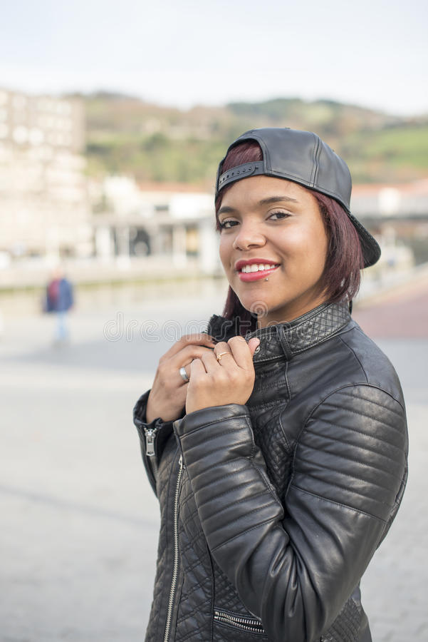 Le den unga latinska kvinnan med baseballmössan i gatan arkivfoton