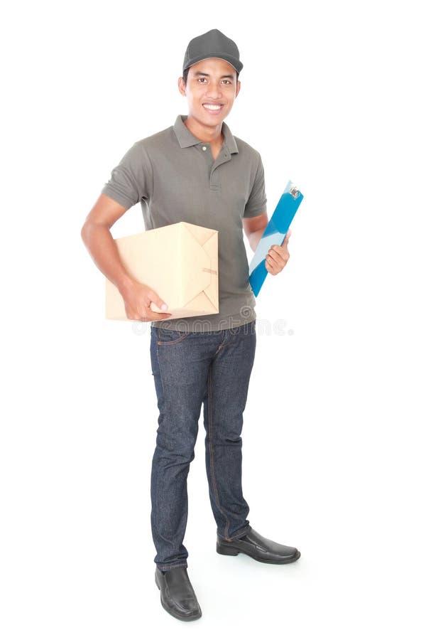 Le den unga leveransmannen som rymmer en cardbox royaltyfri fotografi