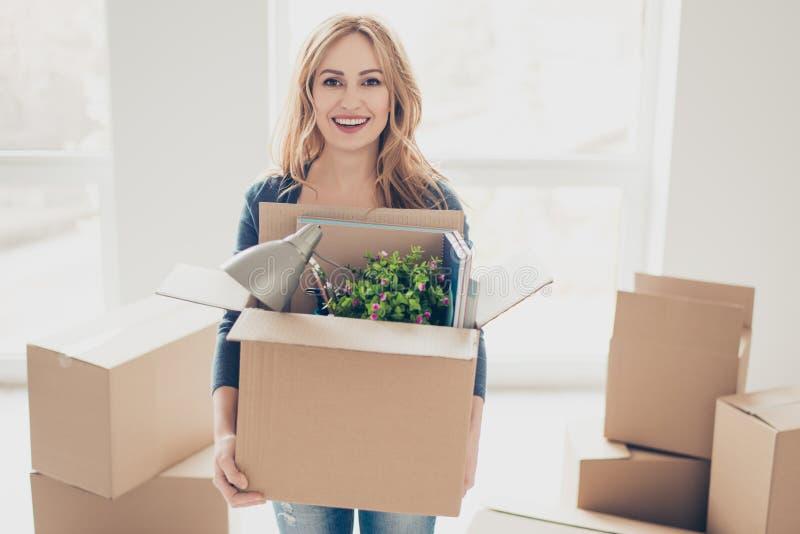 Le den unga lyckliga kvinnan som flyttar det nya stället av att lämna och holdin royaltyfri bild