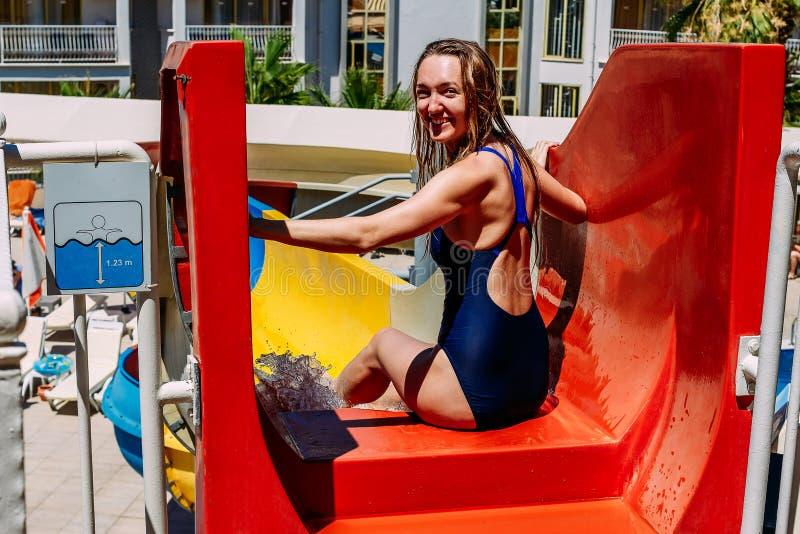 Le den unga lyckliga kvinnan som ner rullar vattenglidbanan i hotellet på sommarsemester royaltyfri fotografi