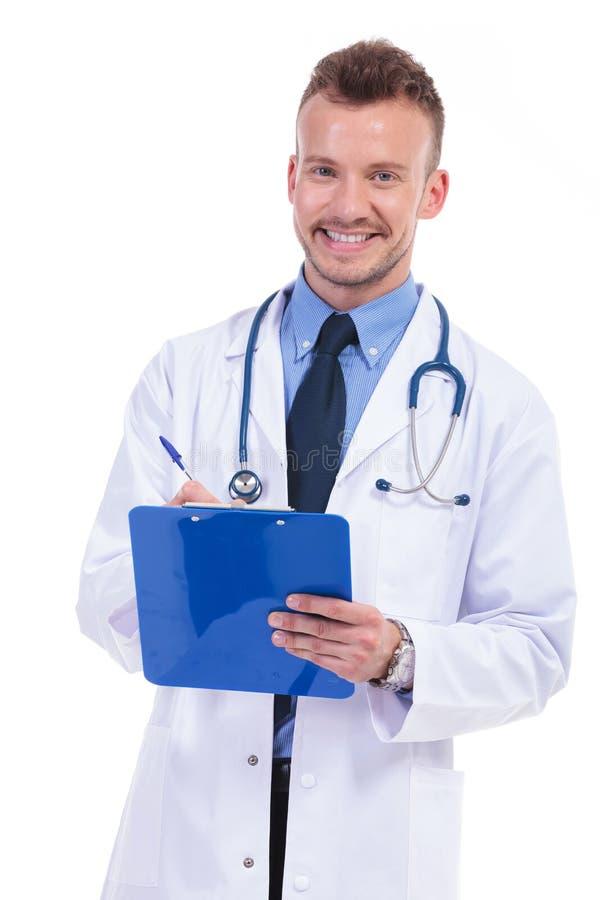 Le den unga manliga doktorn som skriver hans anmärkningar royaltyfria foton