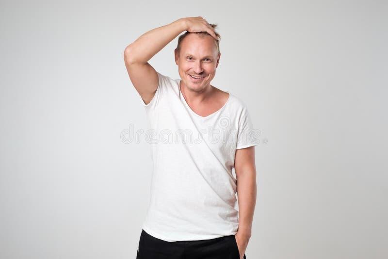 Le den unga mannen i det vita t-skjorta anseendet mot det vita bakgrundsbegreppet av den självsäkra mannen royaltyfri bild