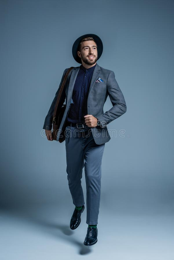 Le den unga mannen i dräkten och hatten som går med läderpåsen arkivfoton
