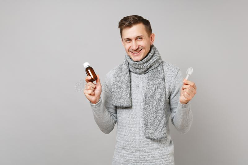 Le den unga mannen i grå tröja, häller halsdukhållen vätskemedicin in i flaskan, sked på grå bakgrund royaltyfri fotografi