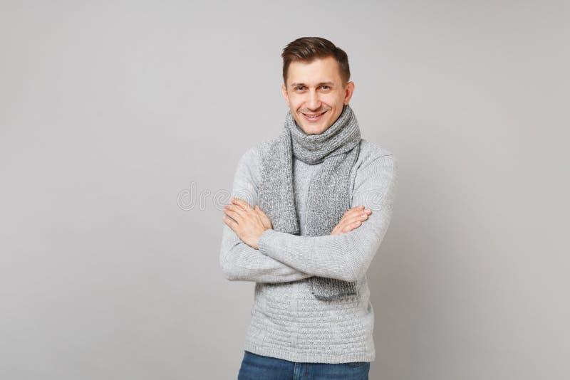 Le den unga mannen i grå tröja, halsduk som rymmer händer vikta på grå bakgrund, studiostående Sunt fotografering för bildbyråer