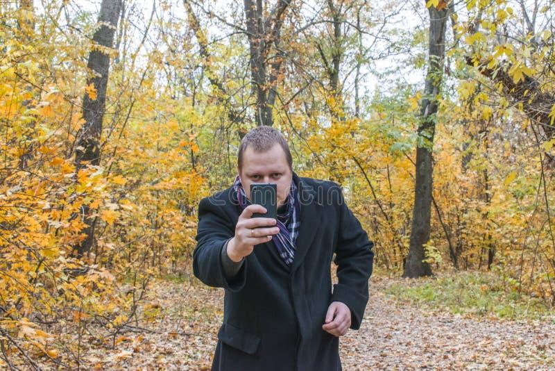 Le den unga mannen i laget som tar bilder på telefonen En man ser telefonen arkivfoto