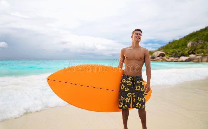 Le den unga mannen med surfingbrädan på sommar sätta på land royaltyfri bild