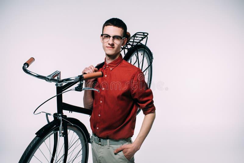 Le den unga mannen som rymmer hans cykel på skuldra royaltyfri bild