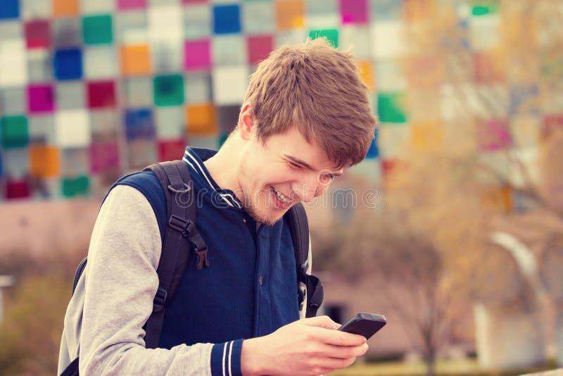 Le den unga mannen som talar på mobiltelefonen i en stad Ung smili fotografering för bildbyråer