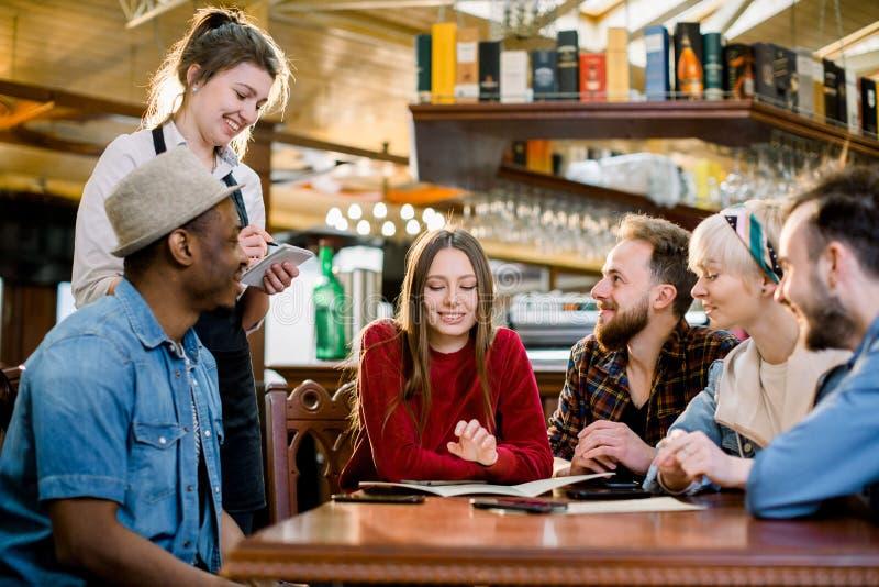 Le den unga servitrins i det svarta förklädet som tar en beställning från klienter i kafé fritid, folk, matkafé och ferier arkivfoto