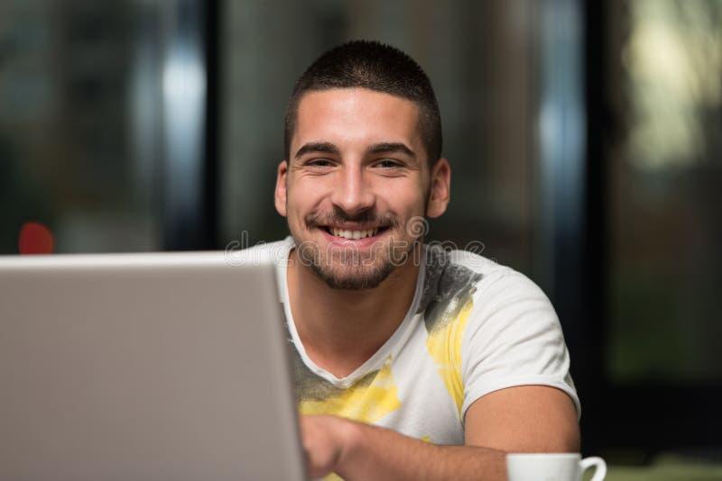 Le den unga studentIn Cafe Using bärbara datorn arkivfoton