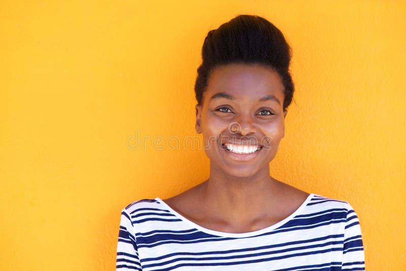 Le den unga svarta kvinnan mot gul bakgrund royaltyfri bild