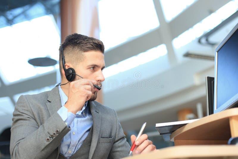 Le den v?nliga stiliga unga manliga call centeroperat?ren arkivfoto