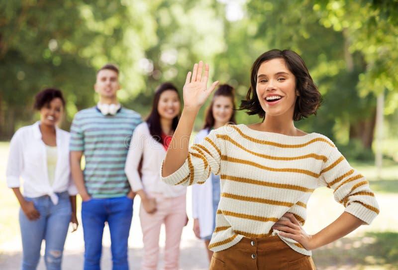 Le den vinkande handen för kvinnan över sommar parkera royaltyfri bild