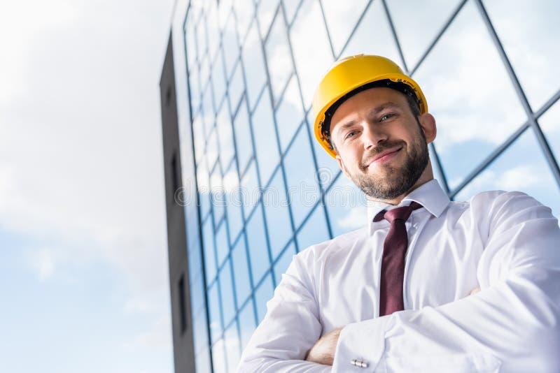 Le den yrkesmässiga arkitekten i hård hatt mot byggnad royaltyfri fotografi