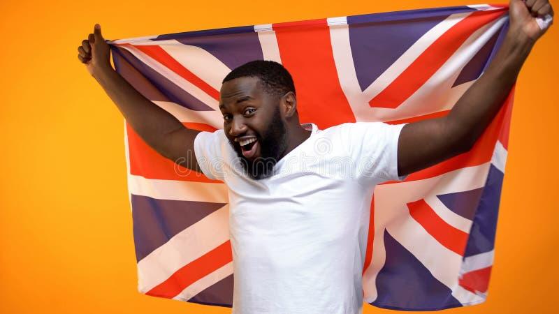 Le denamerikan mannen som firar den nationella festivalen som rymmer den brittiska flaggan arkivbilder