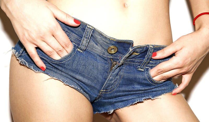 Le denim court-circuite sur les mains bleues de fille dans des poches image libre de droits