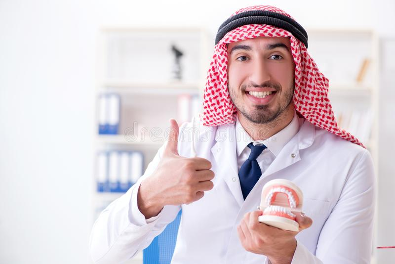 Le dentiste arabe travaillant au nouvel implant de dents images stock