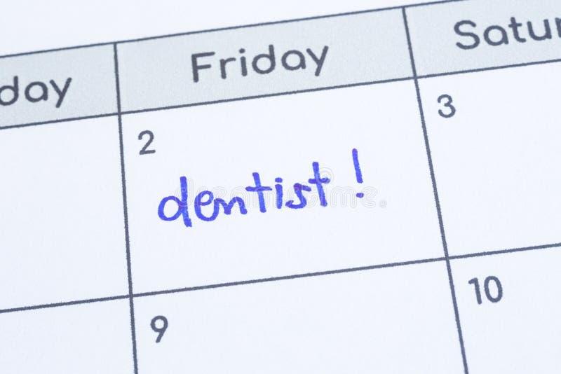 Le dentiste de mot écrit sur la page de calendrier photo libre de droits