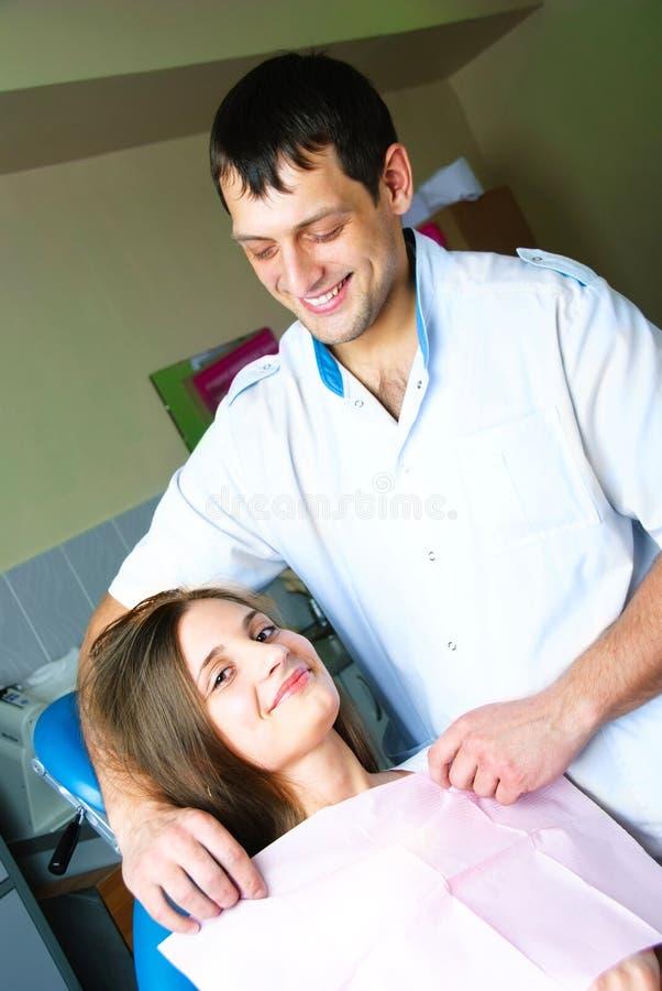 Le dentiste et sien patien dans le bureau photos stock