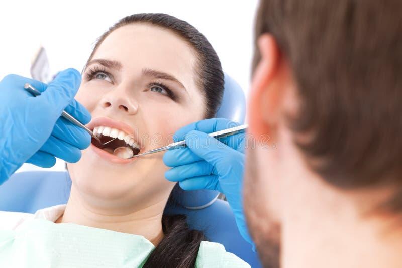 Le dentiste examine la cavité buccale du patient photo stock