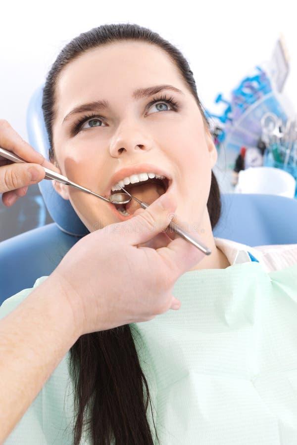 Le dentiste examine la cavité buccale du patient photo libre de droits