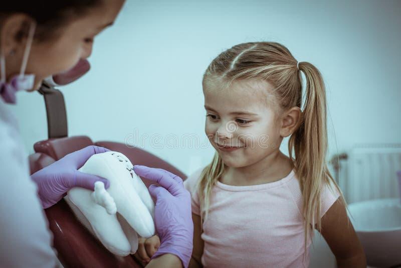 Le dentiste expliquent l'hygiène de dents de petite fille images stock