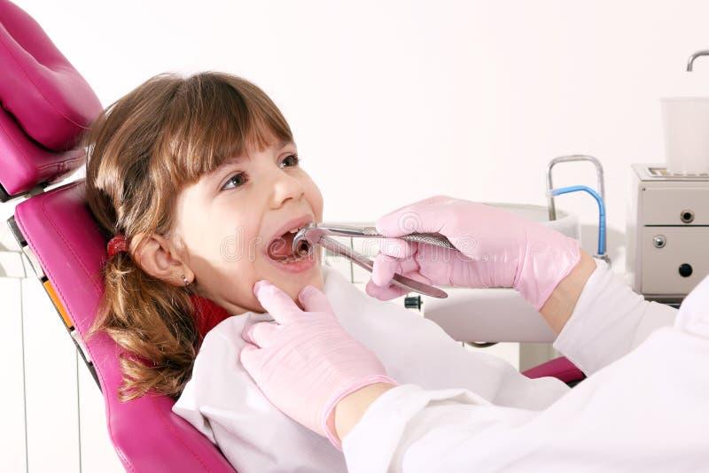 Le dentiste a extrait la petite fille de dent photos libres de droits