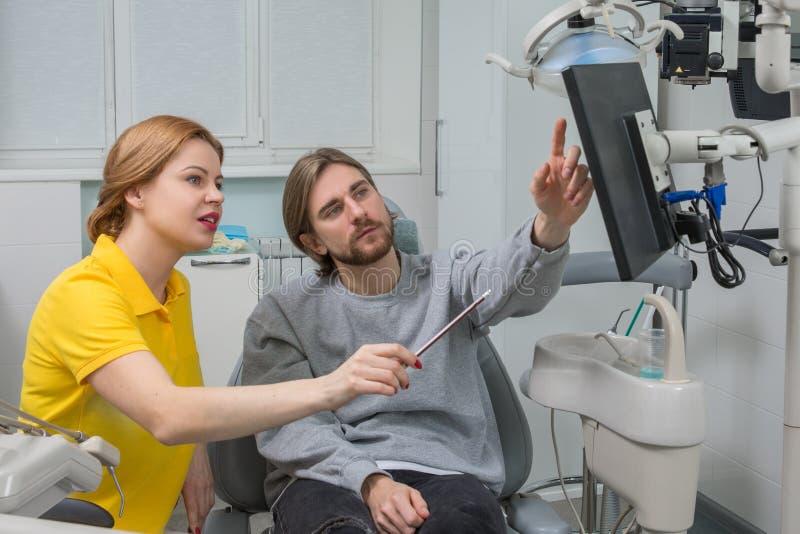 Le dentiste montre un rayon X patient Concept de soins dentaires L'inspection dentaire est donnée au bel homme entouré par le den photos libres de droits
